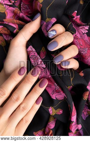 Beautiful Womans Hand With Purple Matte Manicure Holding Fabric