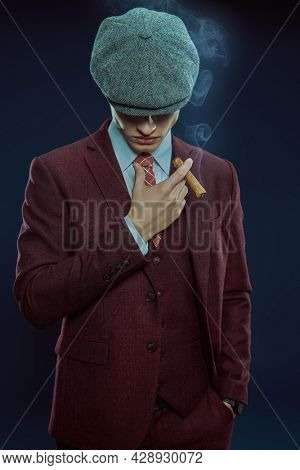 Portrait of young man in an suit and a cap smoking a cigar on a dark background. Retro style, mafia man. Men's beauty, fashion.