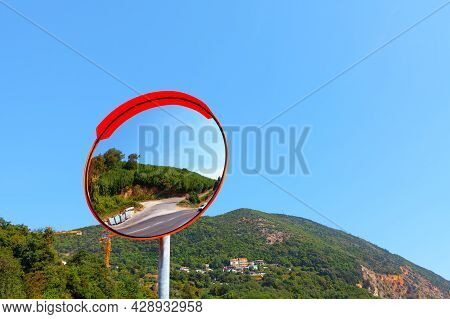 Outdoor Traffic Mirror With Mountains On Background . Curved Mirror.  Round Mirror For Blind Spots O