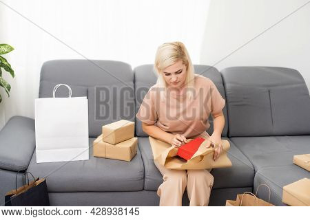 Smiling Satisfied Young Woman Customer Sit On Sofa Unpack Package Open Parcel, Happy Woman Consumer