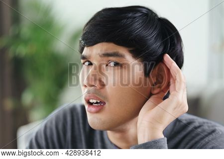 Young Asian Deaf Disabled Man Having Hearing Problems Holds His Hand Over The Ear, Listens Carefully