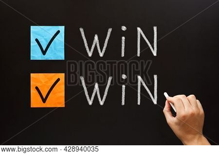 Hand Writing Win-win Situation Business Concept With White Chalk On Blackboard.