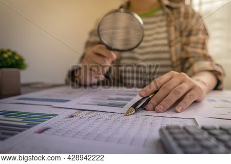 Businesswomen Using Magnifying To Review Balance Sheet Reports. Internal Audit, Analyze Return On In