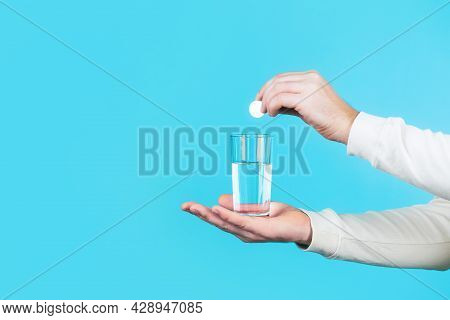 White Pill And A Glass Of Water In Man Hands. Health Concept. Close Up Of Man Holding A Pill. Glass