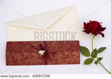 Wedding Invitation With Gold Wedding Decorative Rings Rose And Envelope On A White Background