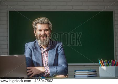 Portrait Of Confident Male Teacher In Classroom. Young Male Teacher With Laptop In Class Sits At The