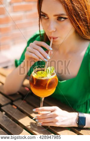 Close-up Face Of Attractive Young Woman Drinking Cocktail Through Straw Sitting At Table In Outdoor