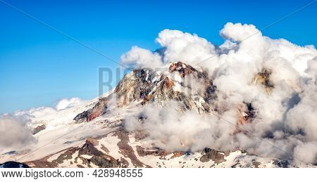 Aerial View From Airplane Of Canadian Mountain Landscape. Sunny Summer Clouds. Mnt Garibaldi Between