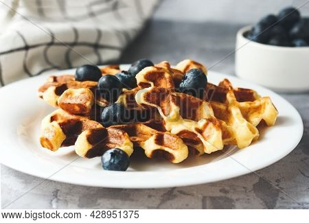 Stack Of Waffles With Blueberries On Grey Background,