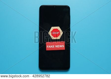 A Picture Of Stop Sign On Hexagon Wood Cut And Fake News At Red Wood On Smartphone. Fake New Caused