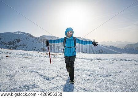Female Climber In The Mountains With Ice Axe. Sunny Day In Mountains.