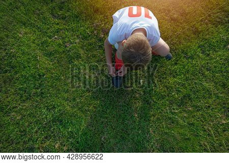 Little Player Is Tying The Shoelaces On The Soccer Field.