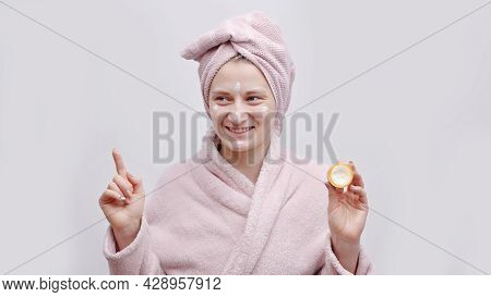 Attractive Girl Holding A Small Jar Of Moisturizing Skin Cream. Applying Cream On Her Face. The Girl