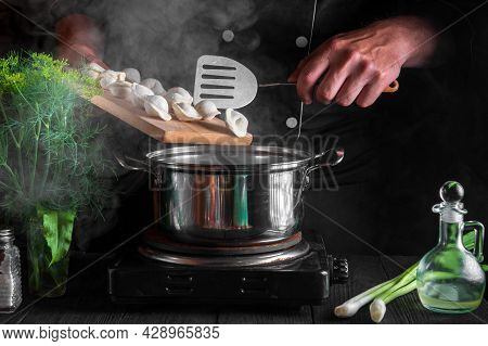 Cook Or Chef Cooks Dumplings In Saucepan In The Restaurant Kitchen. Close-up Of Hands Of The Cook Du
