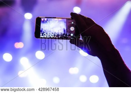 Man Hands Silhouette Taking Photo Or Recording Video Of Live Music Concert With Smartphone In Front