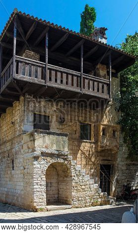 An Old Stone And Wood Romanesque Building In The Historic Medieval Coastal Town Of Porec In Istria,