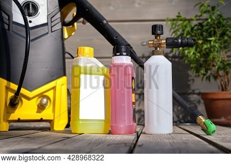 Mini Household High-pressure Washer For Washing A Car Against The Background Of A Gray House And A W