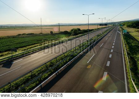Empty Silent Freeway. Asphalt Highway Road With Beautiful Sunset Sky In Pastoral Rural Environment