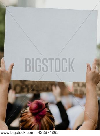 Woman holding a white placard with copy space at a black lives matter protest