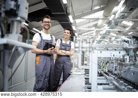 Portrait Of Production Line Workers Controlling Manufacturing Process Of Modern Packaging Industrial