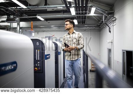 Print House Worker Or Supervisor Controlling Printing Process And Imprint Quality On Modern Offset M