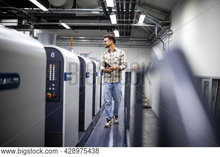 Professional Graphic Designer Supervisor Controlling Printing Process On Modern Offset Print Machine