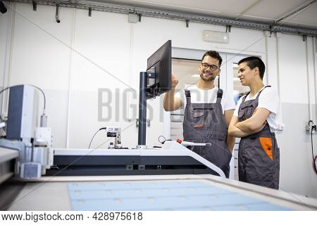 Experienced Technician Training New Worker To Operate Cnc Industrial Machine In Factory.