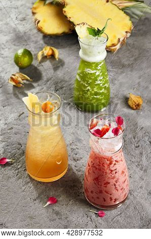 Summer lemonade cocktails glass decorated with fruit slice, lemon slices and berries. Beach cafe beverages, nonalcohol drinks with crushed ice. Lemonade ingredients on gray vintage table