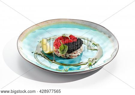 Yin yang salad topped with red and black tobiko. Japanese seafood salad with crab meat, avocado. Salad garnished with oil and spinach leaves, lemon slice. Restaurant plate isolated on white background