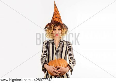 Halloween Holidays. Woman In Witch Hat With Pumpkin. 31 October. Beautiful Woman In Witches Costume