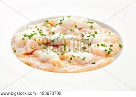 Delicious scallop ceviche with white sauce and green onion on white restaurant plate. Fish Peruvian seafood dish. Scallop ceviche, restaurant seafood plate. Healthy meal.