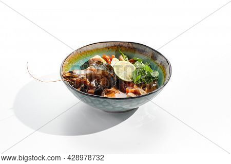 Tom yum or tom yam - hot and sour Thai soup with mixed seafood. Thai traditional soup with shrimps and coconut milk. Tom yum on white background. Isolated soup plate over white background.