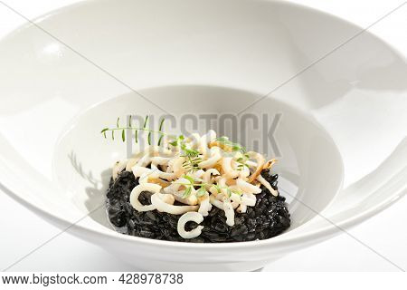 Risotto with cuttlefish black ink. Black risotto plate isolated on white background. Risotto with squid ink topped with calamari rings. Gourmet restaurant dish over white background