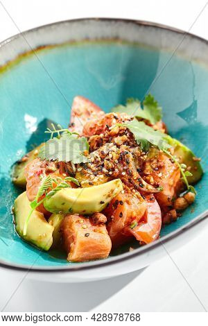 Salmon and avocado salad bowl. Blue salad bowl isolated on white background. Salad garnished with micro greens and sesame, chopped salmon, sliced avocado and parsley green leaf. Raw salmon spicy sauce