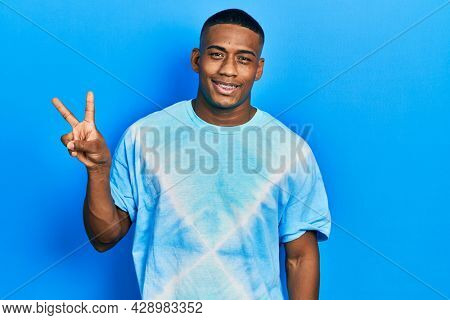 Young black man wearing tye die t shirt smiling with happy face winking at the camera doing victory sign. number two.