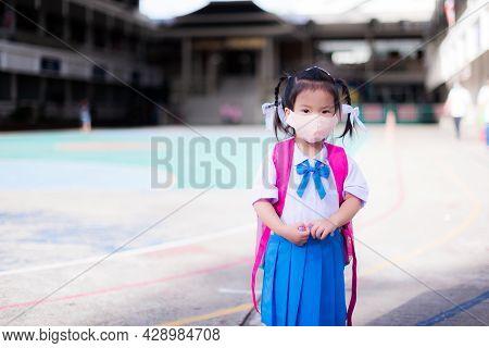 Child Back To School Concept. Girl Wearing Cloth Face Mask. Kid Shoulder Pink Bag. Children Wearing