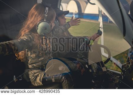 Preteen Girl With Arms Outstretched To Side Sitting In Helicopter Cockpit