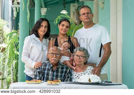 Elderly Couple Sitting. A Man A Woman And A Young Woman With A Child In Their Arms Standing Behind T