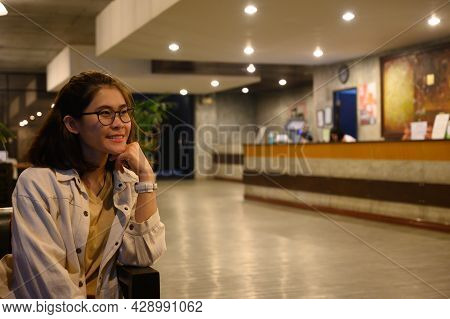 Portrait Of Young Visitor Woman Sitting On Chair And Waiting For Someone At The Hotel Lobby. Hotel L