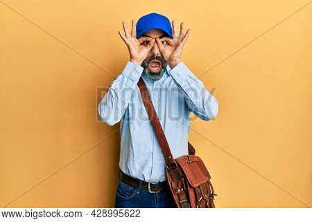 Middle age man with beard and grey hair wearing delivery courier cap doing ok gesture like binoculars sticking tongue out, eyes looking through fingers. crazy expression.