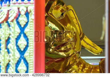 Closeup Of A Shiny Bronze Buddha Statue With A Smiling Face, With Pattern And Ornament In The Foregr