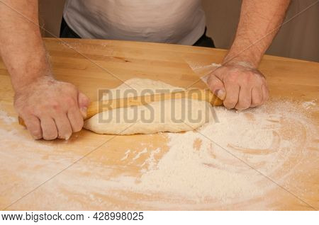 Man's hands are rolling out dough in flour with rolling pin in her home kitchen. Homemade pizza, noodle or pasta production by father.