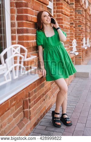 Vertical Full Length Portrait Of Laughing Young Woman Talking On Mobile Phone Standing Leaning On Re