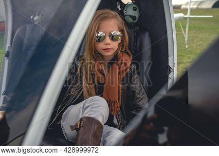 Tween Girl In Mirrored Sunglasses Sitting In Open Helicopter