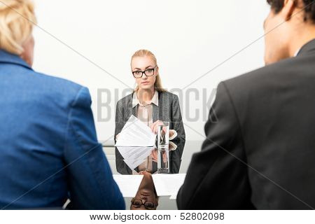 Applicant facing the human resource panel during her job interview, nervously flipping through her resume