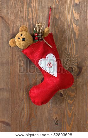Red Christmas stocking filled with a handmade teddy bear and gifts hanging by a rusty nail in an old door.