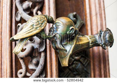 Decorative antique, metal door handles with bird pattern.