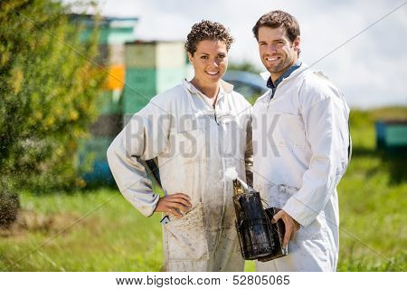Portrait of happy male and female beekeepers with smoker standing at apiary