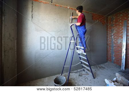 A worker with spatula on a ladder makes repairs smears on the wall putty