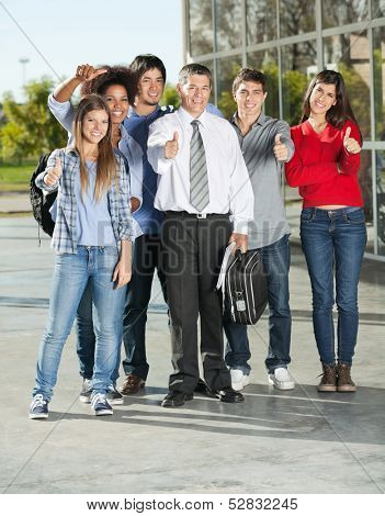 Full length portrait of confident college students and professor gesturing thumbsup on campus